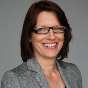 Frau mit mittellangen braunen Haaren und Brille schaut mit offenem Lächeln in die Kamera
