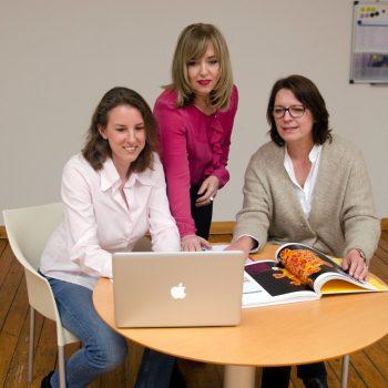 3 Frauen schauen auf einen Laptop in ihrer Textagentur.